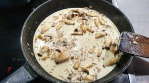 Angebratene Pilze mit Sahne abgelöscht in einer Pfanne.