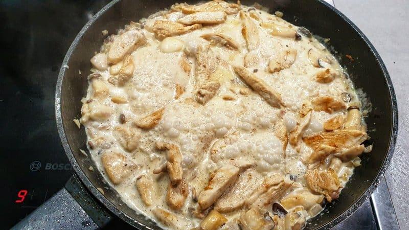 In einer Pfanne kocht helle Soße mit Hähnchen Streifen für Chicken Alfredo.