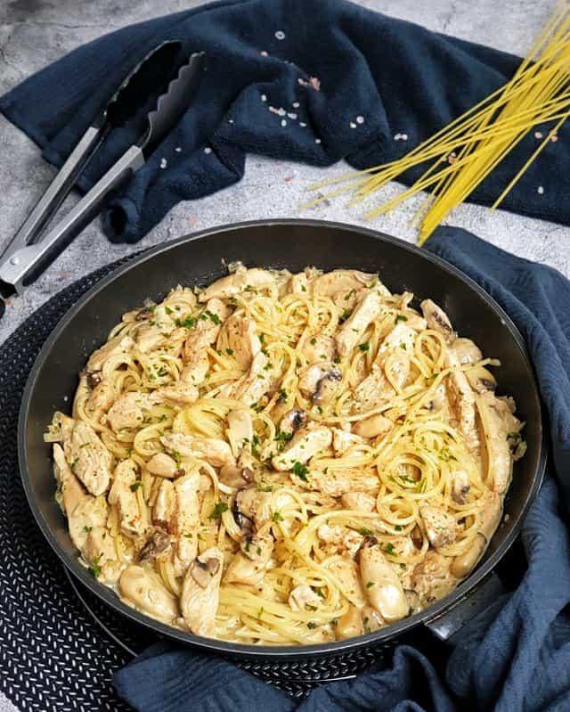 In einer schwarzen Pfanne zu sehen Chicken Alfredo, ein Nudelgericht mit Hähnchenstreifen, Sahne-Soße und Pilzen. Hinter der Pfanne auf einem dunklem Handtuch dekorativ ein paar Spaghetti Nudeln und eine Zange zu sehen.
