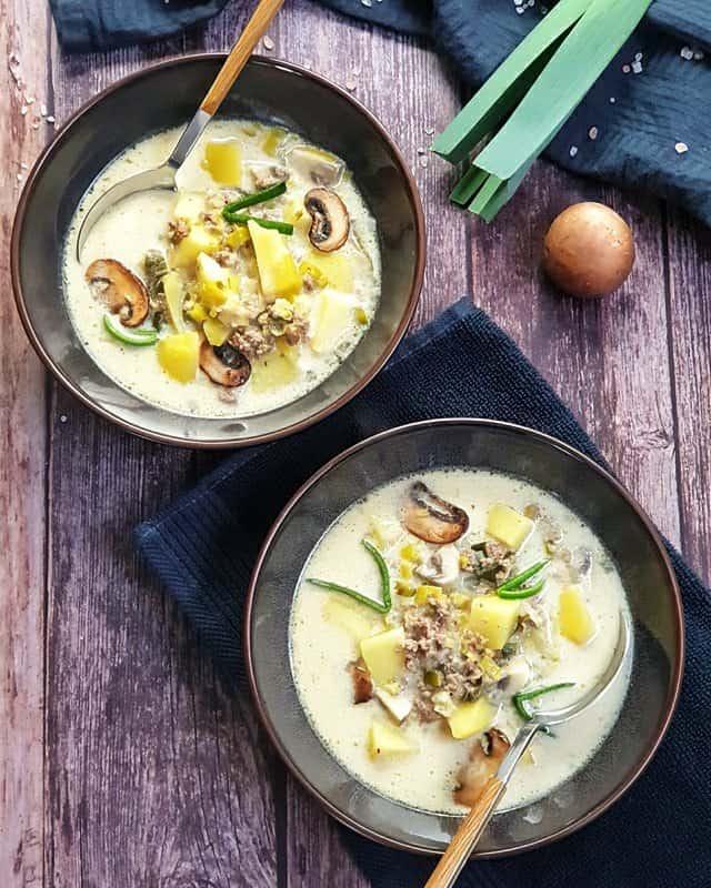 Zwei braune Suppenschälchen, gefüllt mit einer Käse-Lauch-Suppe. Im Hintergrund sieht man eine Stange Lauch, eine Zwiebel und Champignons, dekorativ auf einem Küchenhandtuch fotografiert.