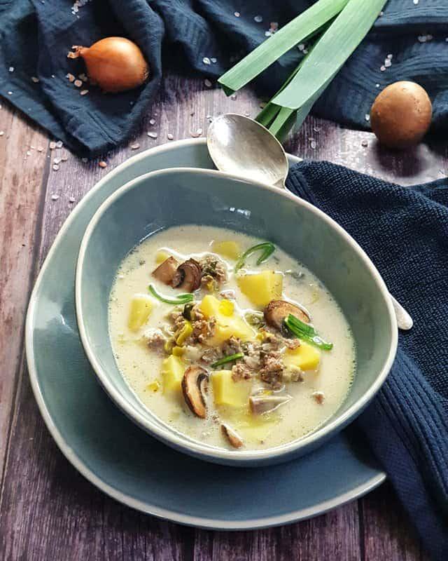 Eine blaue Suppenschale auf einem blauen ovalen Platzteller, gefüllt mit einer Käse-Lauch-Suppe. Im Hintergrund sieht man eine Stange Lauch, eine Zwiebel und Champignons, dekorativ auf einem Küchenhandtuch fotografiert.