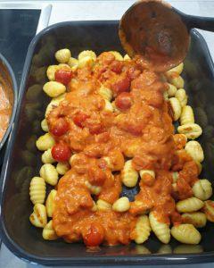 Die fertige Soße wird über die angebratenen Gnocchi in die Auflaufform gegeben.