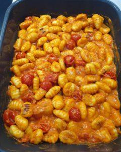 Die Gnocchi sind mit der Tomatensoße vermischt in der Auflaufform zu sehen.