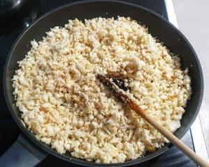 In einer Pfanne zu sehen wie der Reis aus zerkleinertem Blumenkohl in Butter angebraten wird.