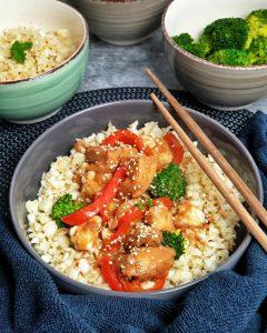In grauen Schale serviert Sesam Hähnchen aus dem Crock Pot auf Blumenkohlreis. Das Hühnchengeschnetzelte ist mit Sesam bestreut und auf dem Rand der Schale sind Essstäbchen drapiert.