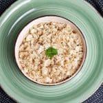 In einer hellen Schale auf einem grünen Teller sieht man angebratenen Blumenkohlreis, schneller Low Carb Reis mit etwas Petersilie als Deko.