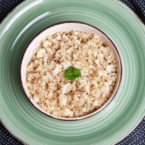 In einer hellen Schale auf einem grünen Teller angebratenen Blumenkohlreis, schneller Low Carb Reis mit etwas Petersilie als Deko.