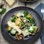 Auf einem braunen Teller angerichtet, ein Gnocchi Salat mit angebratenen Pilzen, frischem Spinat und gehobeltem Parmesan.