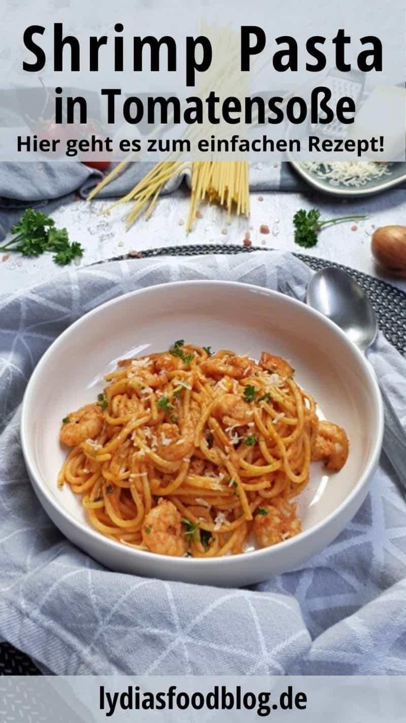 In einer weißen, runden Schale angerichtet sind Spaghetti mit Garnelen und Tomatensoße. Die Spaghetti sind mit Petersilie und Parmesan bestreut und dekorativ fotografiert. Neben dem Teller liegt ein schwarzes Besteck. Im Hintergrund sieht man rohe Spaghetti, geriebenen Parmesan auf einem Teller und Tomaten.