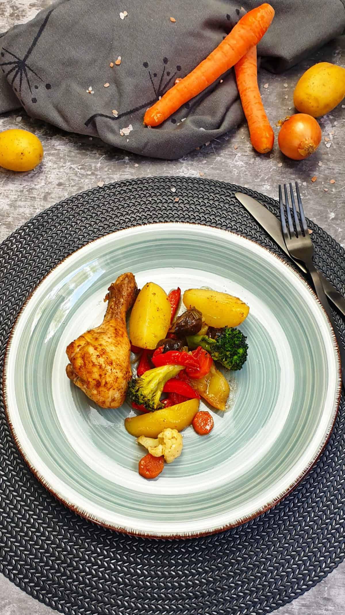 Auf einem türkisfarbenen Teller ein Hähnchenschenkel mit buntem Gemüse und Kartoffeln aus dem Ofen. Im Hintergrund Deko.