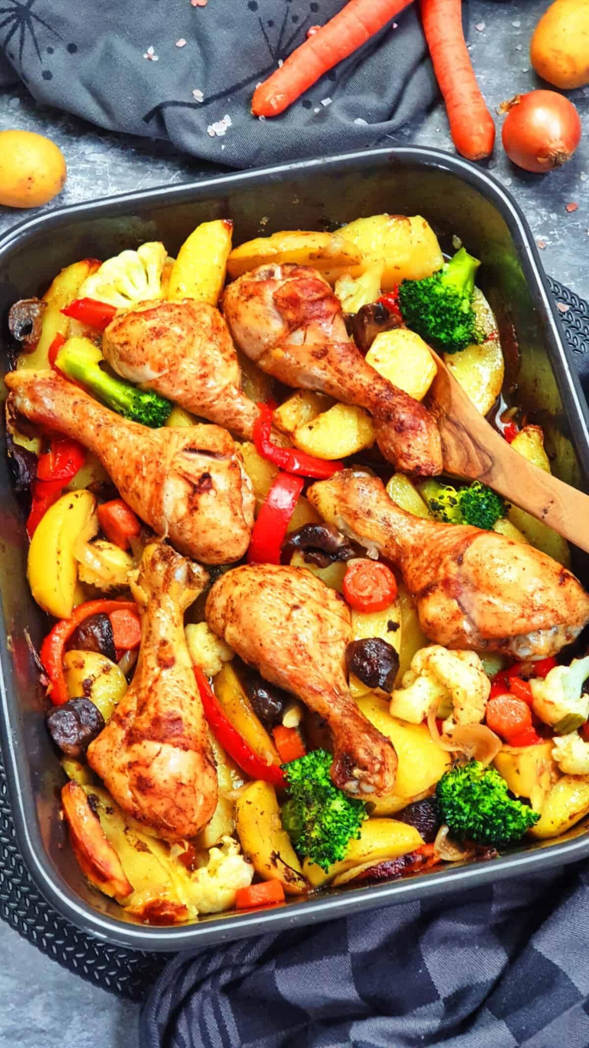 In einer dunklen Auflaufform Hähnchenschenkel mit buntem Gemüse und Kartoffeln aus dem Ofen. Im Hintergrund Deko.