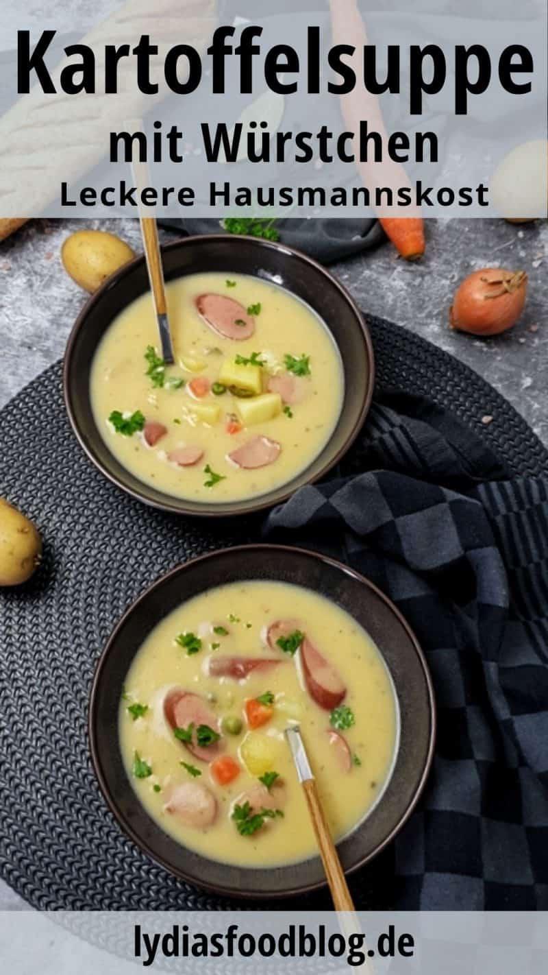 In zwei braunen Schalen angerichtet sieht man Kartoffelsuppe mit Würstchen. In die pürierte Suppe ist etwas Gemüse gegeben und die Suppe ist mit Petersilie bestreut. In den Schälchen stecken Löffel mit Holzgriff. Im Hintergrund sieht man ein Baguette, ein paar Kartoffeln und eine Möhre.