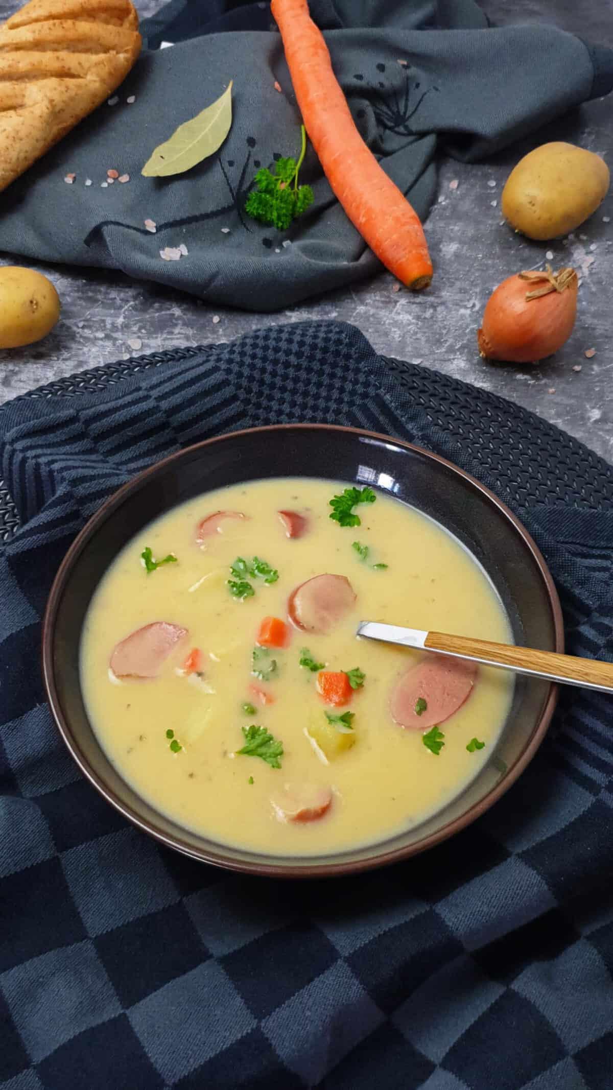 In einer braunen Schale dekorativ angerichtet eine cremige Kartoffelsuppe mit Würstchen sowie Kartoffel und Gemüsestücken. Im Hintergrund auf einem Handtuch liegt ein Baguette, eine Möhre und Kartoffeln.