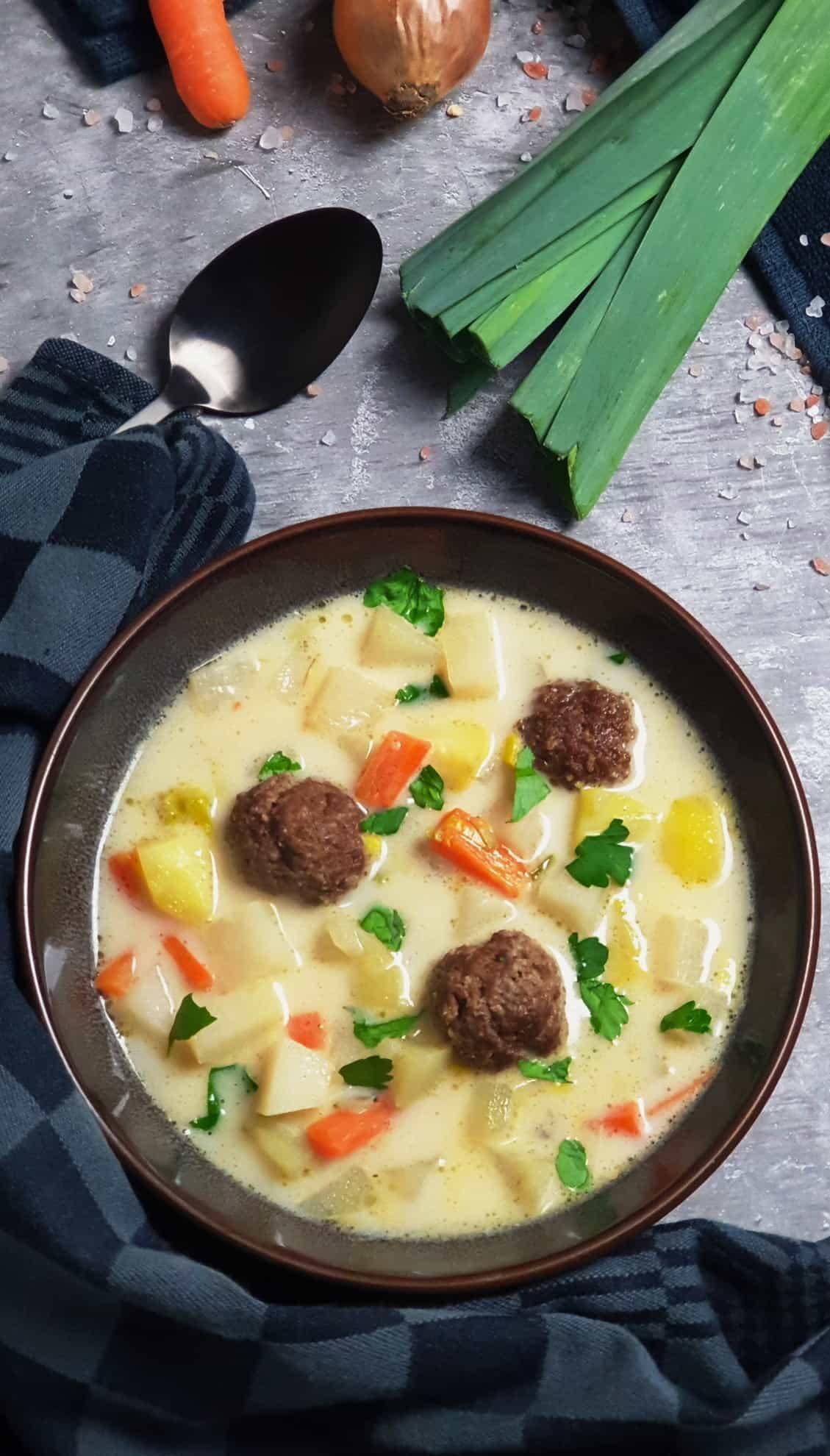 In einer braunen Schale Kohlrabi Suppe mit Hackfleischbällchen. Im Hintergrund Deko.