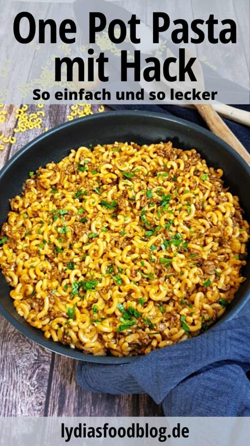 In einer schwarzen Pfanne sieht man das One Pot Pasta Gericht mit Hackfleisch. Um die Pfanne ist ein dunkel graues Küchenhandtuch gelegt. Auf dem Handtuch liegt ein Holzlöffel. Verstreut um die Pfanne sieht man kleine Hörnchennudeln.