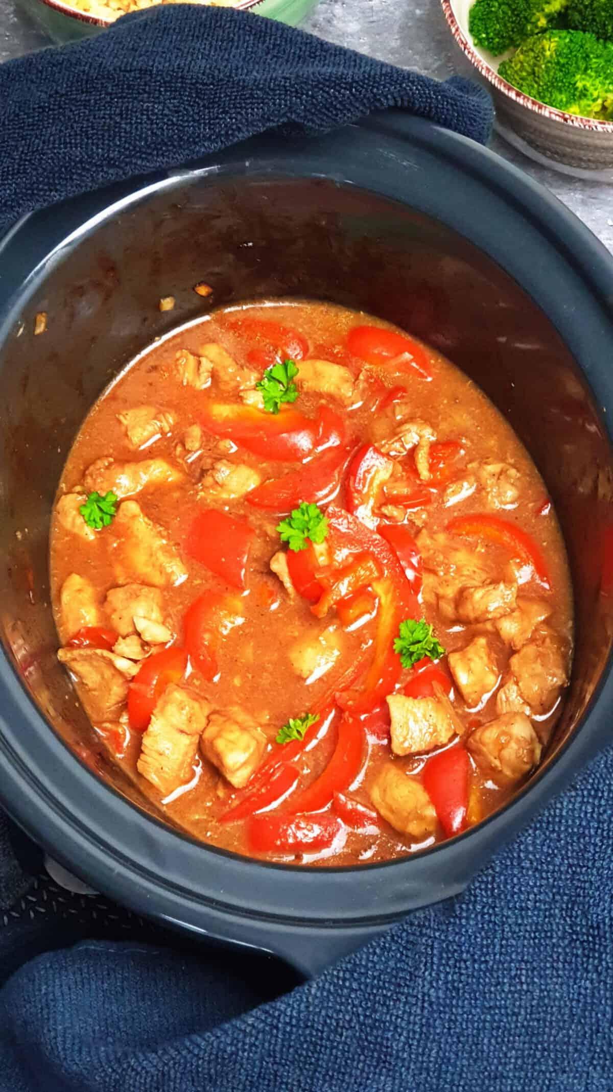 Im Crock Pot Sesam Hähnchen mit Petersilie bestreut. Im Hintergrund Deko.