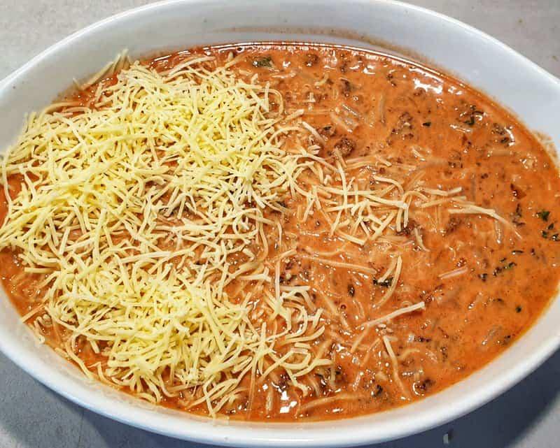 In einer Auflaufform Makkaroni und Tomatensoße zur Hälfte mit Käse bestreut.