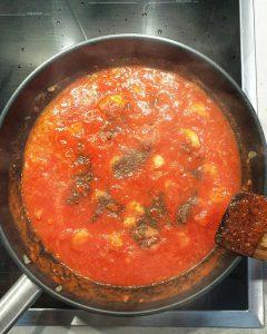 Garnelen mit Tomatensoße und Gewürzen in einer Pfanne.