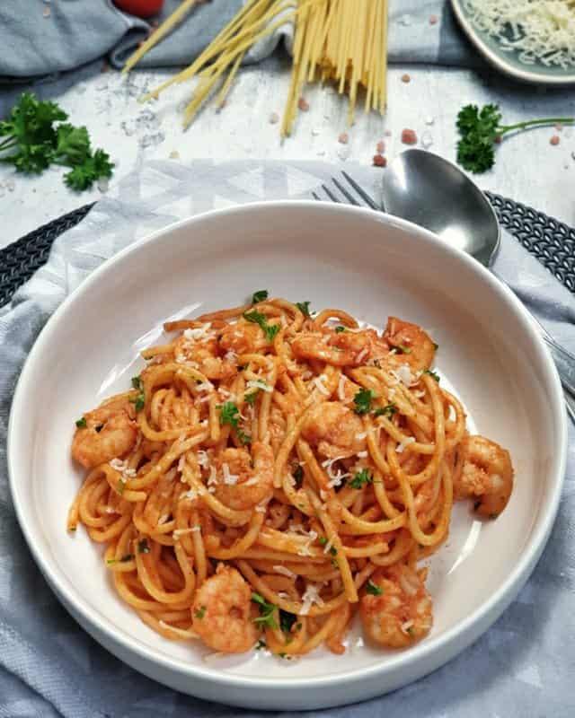 In einer weißen, runden Schale angerichtet Spaghetti mit Garnelen und Tomatensoße. Die Spaghetti sind mit Petersilie und Parmesan bestreut. Neben dem Teller liegt ein schwarzes Besteck. Im Hintergrund Deko.
