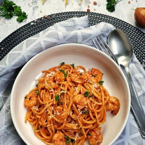 In einer weißen, runden Schale angerichtet Spaghetti mit Shrimps und Tomatensoße. Die Spaghetti sind mit Petersilie und Parmesan bestreut. Neben dem Teller liegt ein schwarzes Besteck. Im Hintergrund Deko.