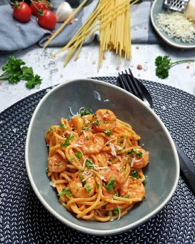 In einer blau grauen, ovalen Schale angerichtet sind Spaghetti mit Garnelen und Tomatensoße. Die Spaghetti sind mit Petersilie und Parmesan bestreut und dekorativ fotografiert. Neben dem Teller liegt ein schwarzes Besteck. Im Hintergrund sieht man rohe Spaghetti, geriebenen Parmesan auf einem Teller und Tomaten.