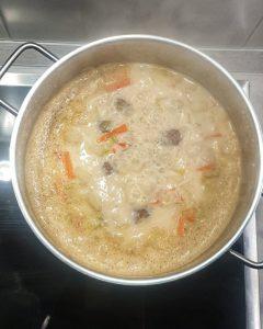 Dier Kohlrabi Suppentopf mit Hackbällchen kocht in einem Topf und ist fertig zum Servieren.