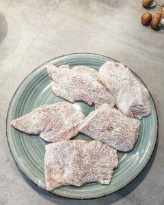 Auf einem Teller sieht man in Mehl gewendete Putenbrust Filets.