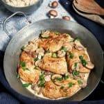 In einer gußeisenen Pfanne sieht man 5 Putenbruststücke in Champignons Rahm Soße. Im Hintergrund ist eine Schale mit Reis und ein paar Champignons zu sehen. Neben der Pfanne liegen 2 Holzlöffel.