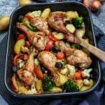 In einer schwarzen Auflaufform sieht man das fertige Hähnchenschenkel mit Gemüse und Kartoffeln aus dem Ofen. Im Hintergrund sind 2 Möhren, ein paar Kartoffeln und eine Zwiebel zu erkennen.