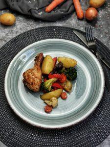 Auf eine blauen Teller angerichtet sieht man einen Hähnchen Unterschenkel mit Ofengemüse.