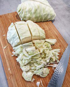 Auf einem Holz Schneidebrett Spitzkohl in Streifen geschnitten. Daneben ein Messer.