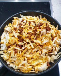 In einer Pfanne in Streifen geschnittener Spitzkohl mit angebratenem Hackfleisch.