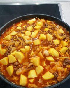 In einer Pfanne in Brühe Kartoffeln, Hackfleisch und Kohl.