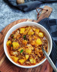 In einer weißen Schale ein Schichtkohl Gericht mit Kartoffeln und Hackfleisch.