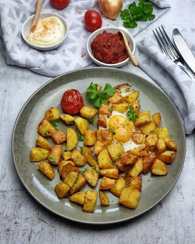 Auf einem grünen Teller angerichtet knusprige Patatas Bravas mit Spiegelei, einer Tomatensoße und Aioli.