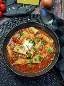 In einer braunen Schale angerichtet eine Lasagne Suppe. Eine rote tomatige Suppe mit Lasagne Platten, Creme Fraiche und Petersilie garniert.