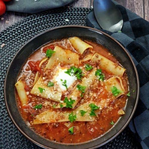 In einer braunen Schale angerichtet eine Lasagne-Suppe mit Hackfleisch. Im Hintergrund Deko.