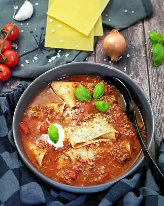In einer grauen Schale angerichtet eine Lasagne Suppe. Eine rote tomatige Suppe mit Lasagne Platten, Creme Fraiche und Petersilie garniert.