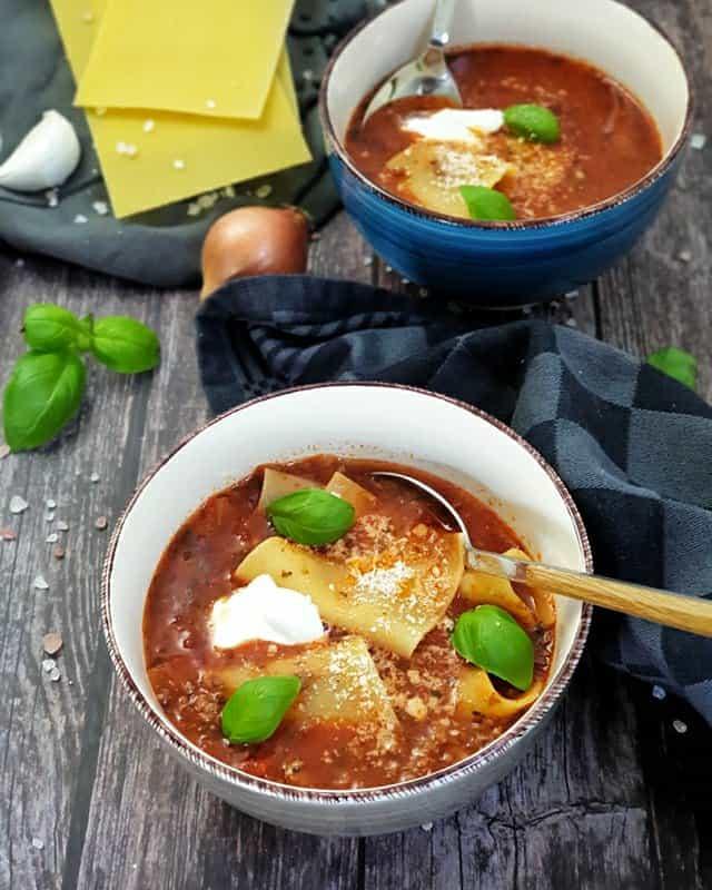 In einer weißen Schale angerichtet eine Lasagne Suppe. Eine rote tomatige Suppe mit Lasagne Platten, Creme Fraiche und Petersilie garniert.