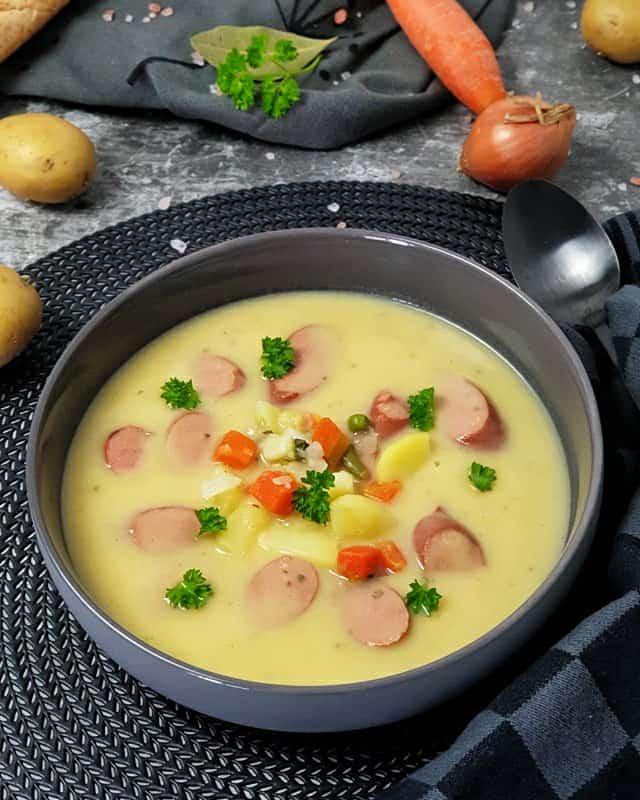 In einer grauen Schale dekorativ angerichtet eine cremige Kartoffelsuppe mit Würstchen sowie Kartoffel und Gemüsestücken. Im Hintergrund auf einem Handtuch liegt ein Baguette, eine Möhre und Kartoffeln.