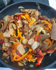 In einer Pfanne wird Gyrosgeschnetzeltes angebraten mit Paprika und Zwiebeln. Das sind die Hauptzutaten für Gyrosgeschnetzeltes mit Reis.