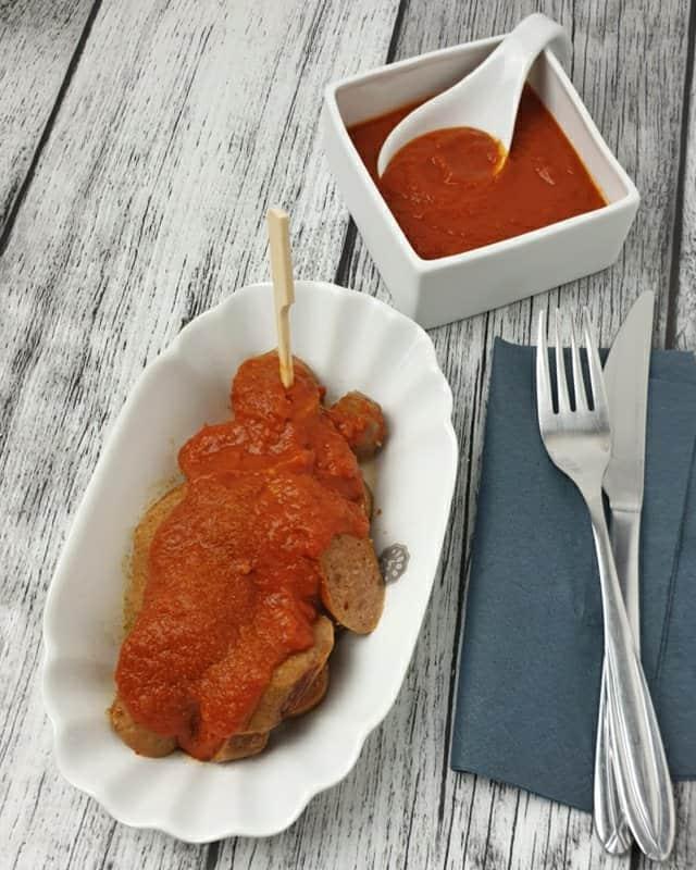 In einer Pommesschale sieht man eine Bratwurst mit selbst gemachter Currysoße. Im Hintergrund steht eine Schale mit Soße.