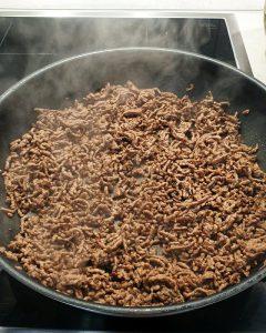 In einer schwarzen Pfanne wird das Hackfleisch für das One Pot Pasta Gericht mit Hackfleisch angebraten.