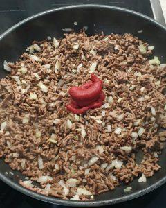 In einer Pfanne angebratenes Hackfleisch mit Zwiebeln und Tomatenmark.
