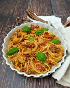 In einer weißen runden Auflaufform sieht man einen Spaghetti Auflauf mit Hackfleisch. Die Nudeln sind zu kleinen Nestern gerollt und mit Basilikum garniert.