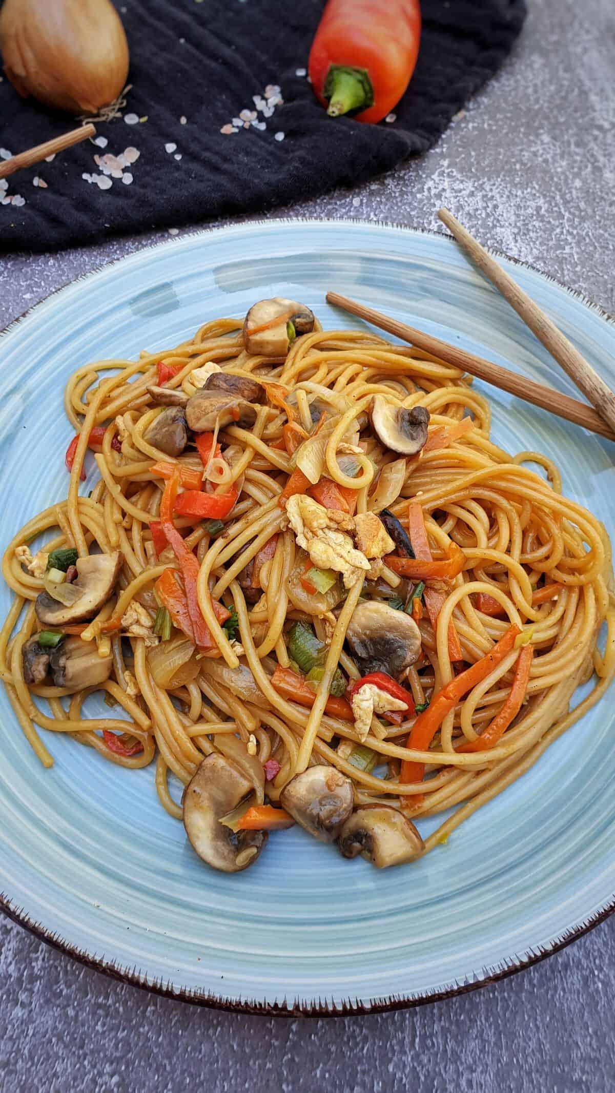 Auf einem blauen Teller angerichtet asiatisch gebratene Nudeln mit Gemüse.
