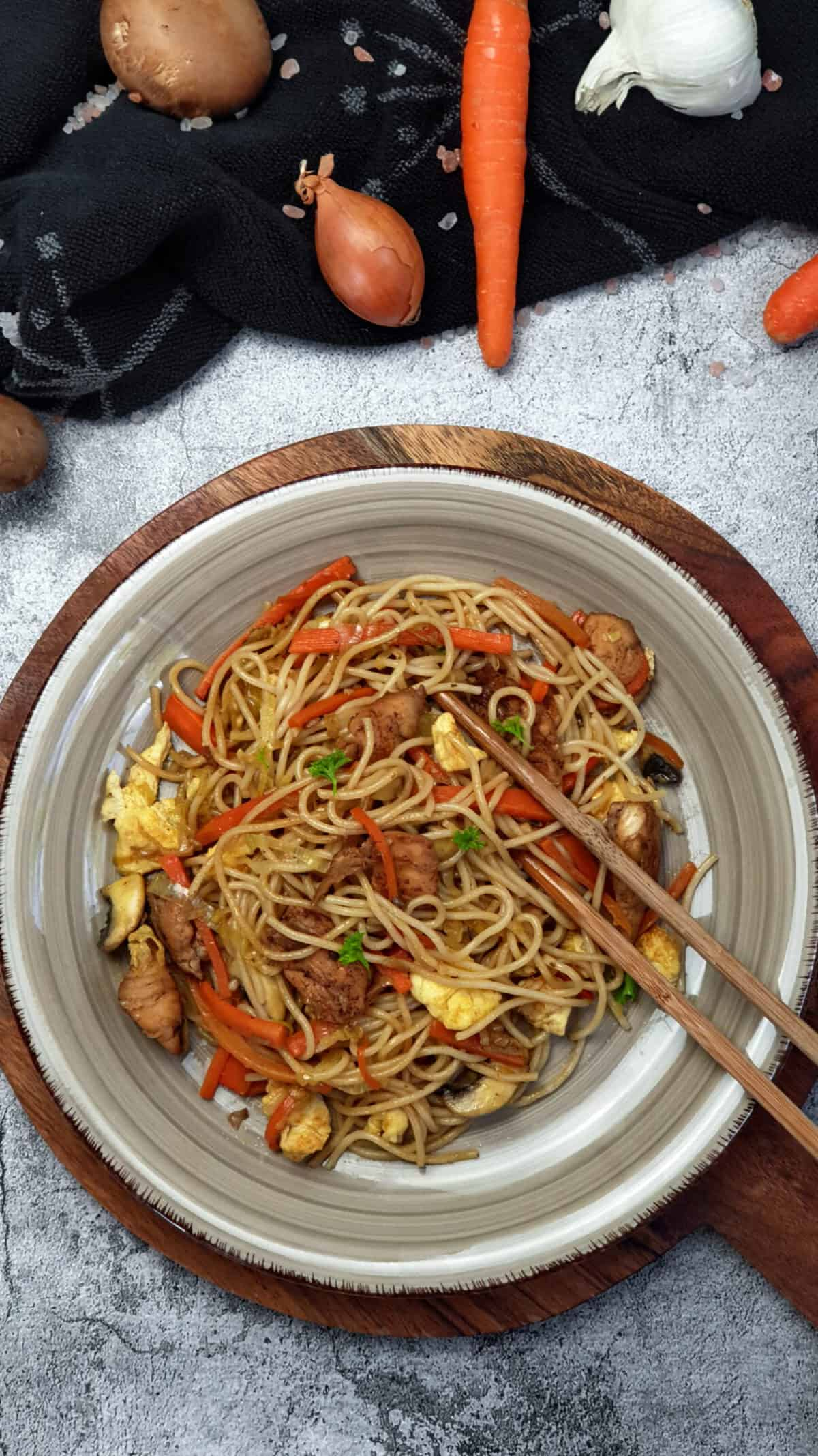 Auf einem braunen Teller Asia Nudeln mit Huhn und Gemüse. Im Hintergrund Deko.
