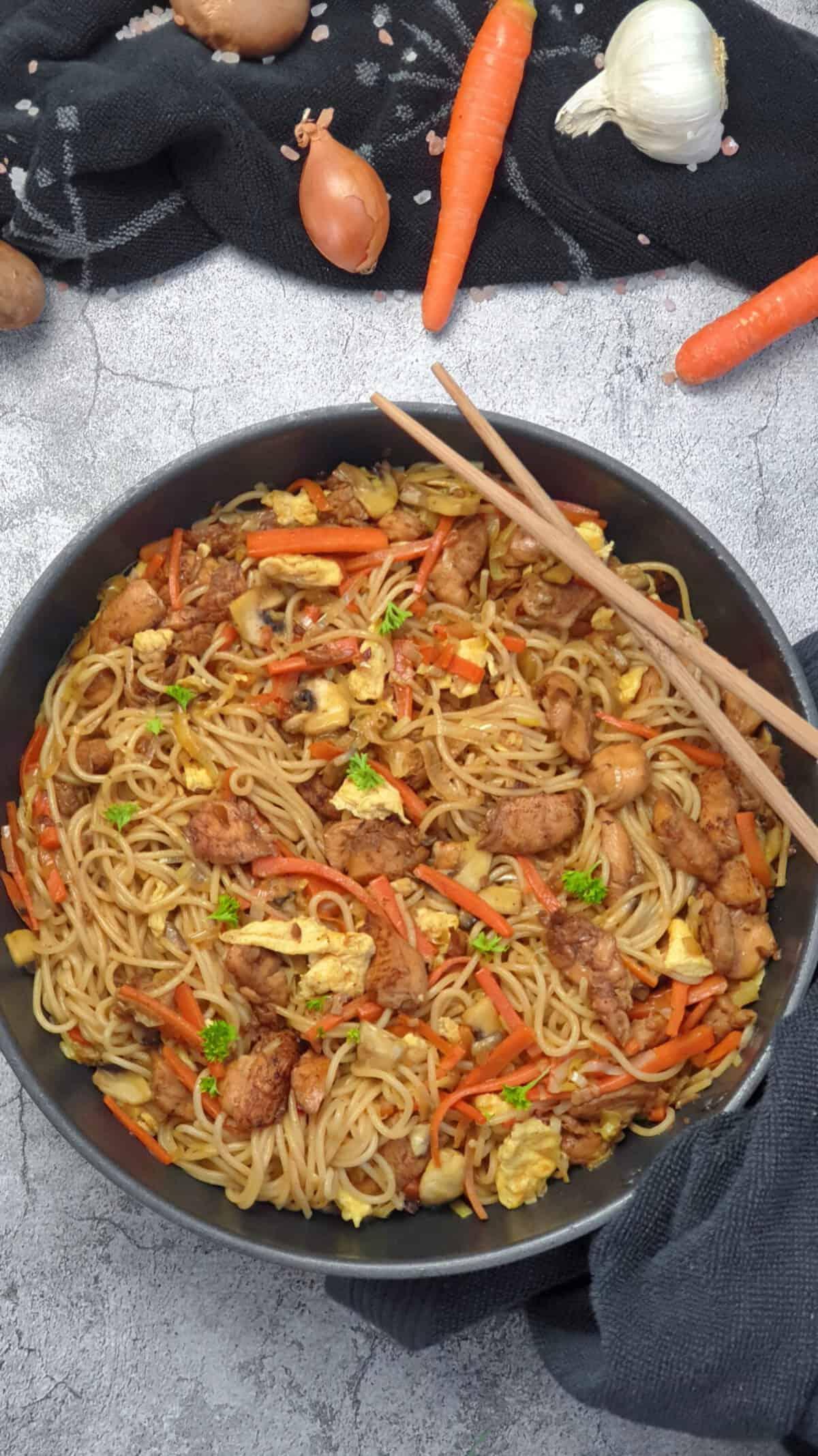 In einer großen schwarzen Pfanne Asia Nudeln mit Huhn und Gemüse. Im Hintergrund Deko.