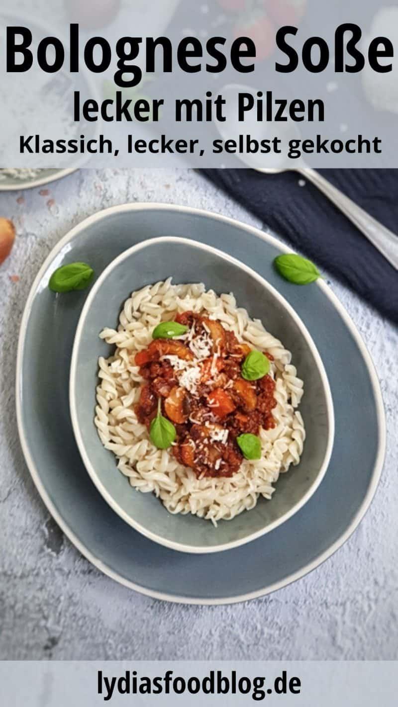 In einer graublauen ovalen Schale angerichtet Bolognese-Soße mit Pilzen und Fusilli. Garniert mit ein paar Basilikum Blättern und etwas geriebenen Parmesan.