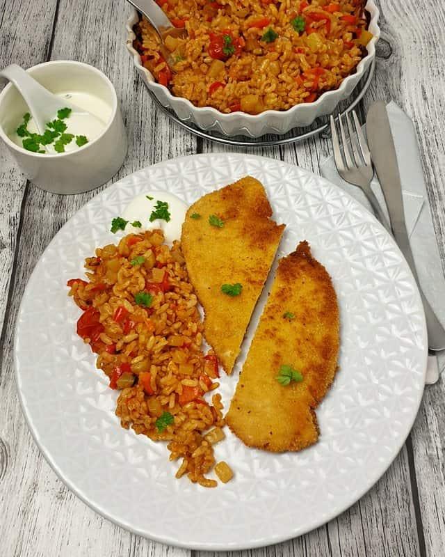 Auf einem weißen Teller liegt ein Schnitzel daneben ist der Ofen Gemüsereis und ein Joghurt Dip zu sehen. Im Hintergrund steht eine Auflaufform mit Gemüsereis sowie ein Schälchen mit dem Joghurt Dip.